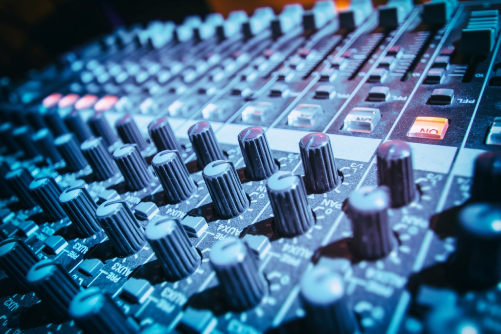 Close-up of DJ's sound mixing desk illuminated by blue light